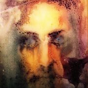 An old print of Jesus, covered in wax, as found in an old chapel.