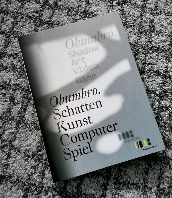 Full cover of the exhibition catalogue. Black typography on a dark and light grey background resembling shadow and light.