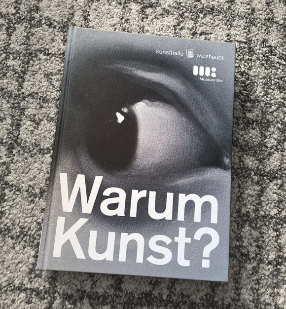 """Cover of the exhibition catalogue """"Warum Kunst?"""". White typography on a black and white drawing on an eye, close-up, looking left."""